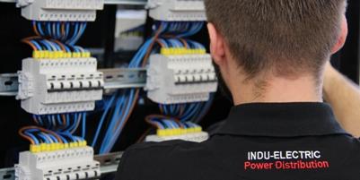 Sie sehen einen Mitarbeiter von INDU-ELECTRIC bei der Arbeit.
